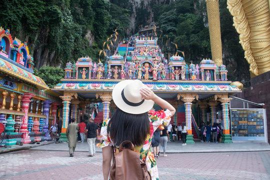 A tourist woman is sightseeing at Batu cave Hindu temple in Kuala Lumpur, Malaysia.
