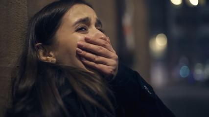 Shocked robber victim crying at night street, panic attack, psychological trauma