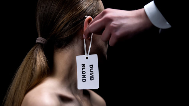 Male hand putting dumb blonde label on female ear, humiliation, stereotypes
