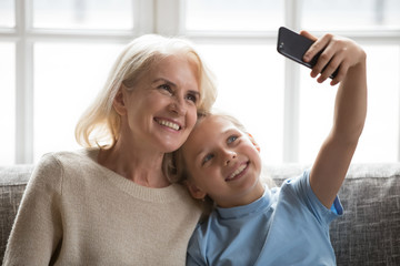Cheerful grandmother and little granddaughter using phone taking selfie