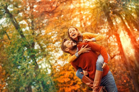 Smiling man carrying woman piggyback outdoor
