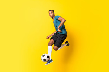 Afro American football player man over isolated yellow background Wall mural