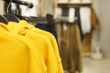Hoodies, a sweater and a hoodie on a hanger in a fashion store for youth.