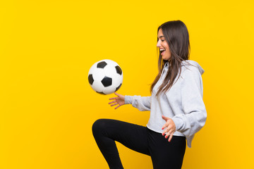 Young football player woman over isolated yellow background
