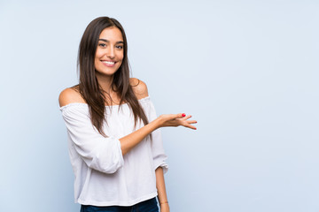 Young woman over isolated blue background extending hands to the side for inviting to come