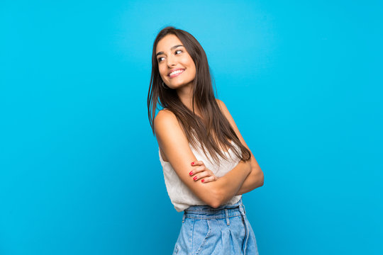 Young woman over isolated blue background Looking front