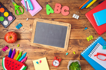 Back to school background with school supplies on wooden table. Top view from above