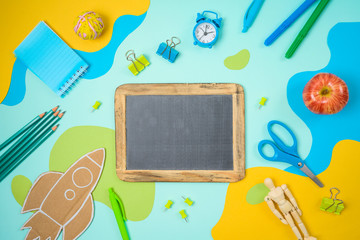 Back to school concept with school supplies and paper flowing shapes background. Top view from above