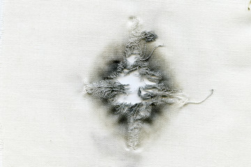 Bullet hole on a white cloth when shot at point-blank range from a 45-gauge weapon, abstract background.