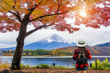Wall Mural - Woman traveler with backpack looking to Fuji mountains in Autumn, Japan.