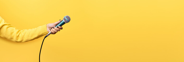 hand holding microphone over yellow background, panoramic mock up image
