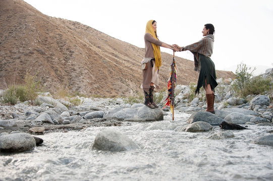 Two wild celebrant women join hands in a bridge over water a flowing river in the wilderness.