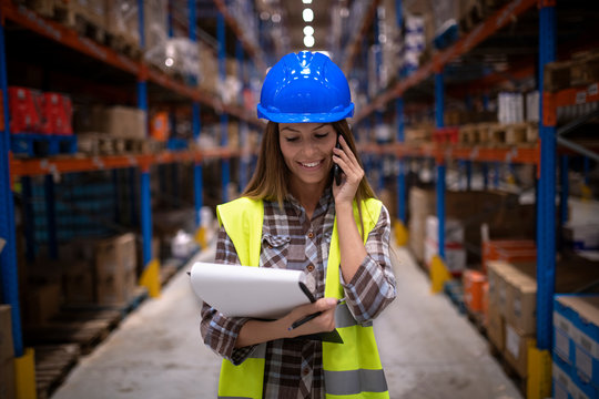 Portrait of beautiful female warehouse worker having conversation on cell phone in large storage distribution center. Organizing distribution and logistics.