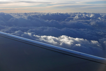 aerial view from plane at clouds with part of wing