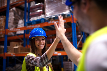 Warehouse workers giving high five to each other. Industrial workers hands touching and clapping for successful job done. Positive atmosphere at job. Teamwork concept.