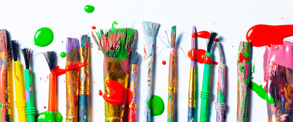 Row Of Messy Colorful Paint Brushes On Isolated White Background - Creativity Concept