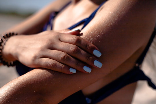 Girl smears sunblock. On the beach uses tanning oil.