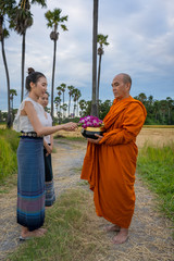 Women in old traditional dress make merit with monk in rural areas according to the beliefs of Buddhism in Thailand