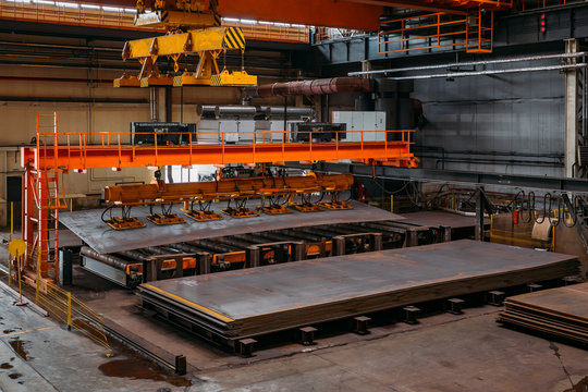 Overhead crane with vacuum handling grippers lifting iron sheets