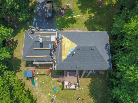 aerial view of roofers replacing shingles
