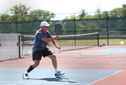 A senior man hits a shot while competing in a pickleball tournament