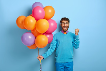 Triumphing joyous young gentleman raises clenched fist, celebrates getting new job, organizes party in office, wears optical glasses, blue sweater and trousers, holds colorful bunch of balloons