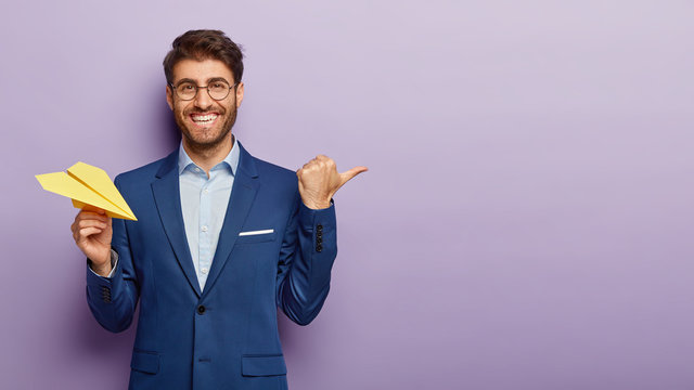 Business success concept. Waist up shot of happy prosperous businessman holds hand made paper airplane, points away with thumb, shows blank space for your promotional content, being in office