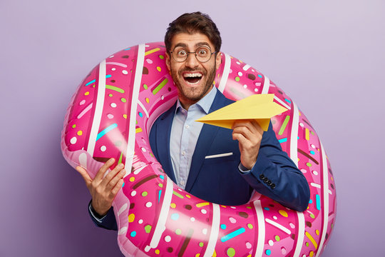 Happy successful employer rejoices coming annual leave, holds paper airplane, poses in inflated swimring, imagines flight to resort place, wears optical glasses and formal suit. Summer is soon