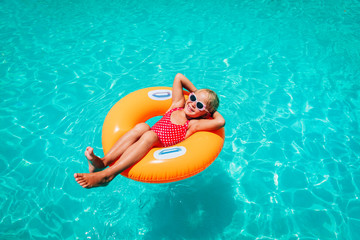 cute little girl have fun at the pool, child relax in floatie