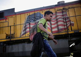 A Central American migrant walks past the image of a U.S. flag on a train during his journey towards U.S. in Saltillo
