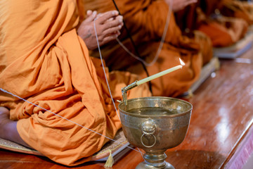 Buddha monk hold candlestick above holy water bowl. religion ceremony. Buddhist holy water. image for copy space.
