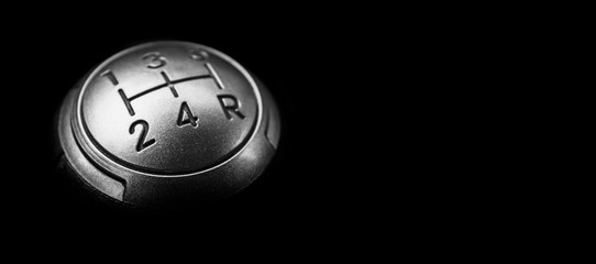 Close up view of a manual gear lever shift isolated on black background. Manual gearbox. Car interior details. Car transmission. Soft lighting. Abstract view. Car detailing