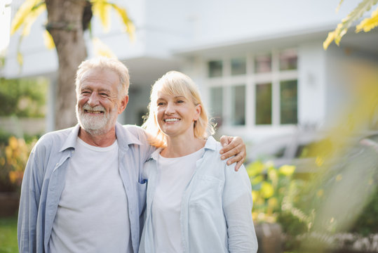 Seniors European couple man and woman are standing at outdoor green garden in retirement home. Retired couple are smiling felling happy and looking out of camera.