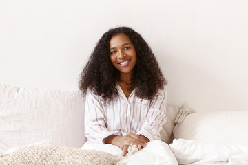 Cute joyful young African female in stylish pajamas relaxing in bed, smiling broadly at camera. Beautiful dark skinned girl with Afro hairstyle spending slow lazy morning at home, having happy look