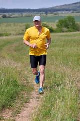 50-es caucasian man running on meadow