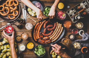 Flat-lay of Octoberfest dinner table concept with grilled sausages, pretzel pastry, potatoes, cucumber salad, sauces, beers and peoples hands with holding snacks over dark wooden background, top view Fototapete