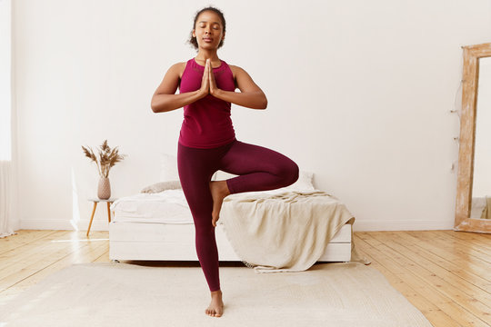 Well being, active lifestyle, health and fitness concept. Portrait of healthy young mixed race woman with strong flexible body, standing upright on carpet, doing tree pose, training balance