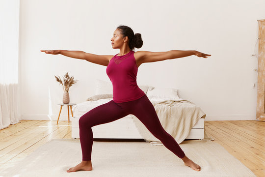 Side view of stylish athletic sporty African girl in leggings and top standing barefooted on floor in warrior 2 pose, doing yoga, strengthening legs, training endurance to get strong healthy body