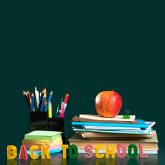Inscription BACK TO SCHOOL. Still life with school supplies. Green background. Notebooks, notebooks, felt-tip pens, colored pencils, an apple. Colorful picture.