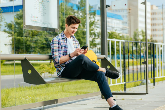 Male student wth smart phone in hands wearing plaid shirt sitting on bench while waiting for transport at tram or bus station.