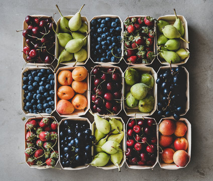 Summer fruit and berry variety. Flat-lay of strawberries, cherries, grapes, blueberries, pears, apricots, figs in wooden eco-friendly boxes over grey background, top view. Local farmers produce