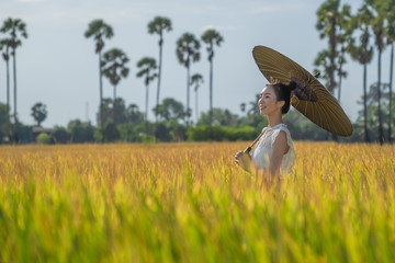 Beautiful Asian girl in traditional dress costume at yellow rice field is important export of Thailand