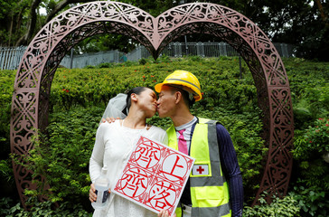 Henry Tong, wearing a helmet and a first aid vest associated with the anti-extradition bill protests, kisses his wife Elaine To as they pose for photos after getting married in Hong Kong