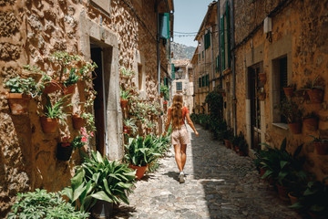 Back view young girl tourist walk through cozy and beautiful  street decorated with flower pots and...