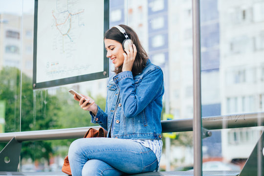 Smiling excited brunette woman wearing blue denim jacket with headphones looking away, relaxing, listening music while waiting at tram stop in a city.