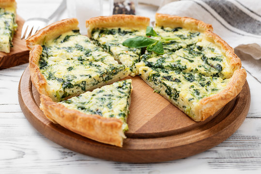 Vegetarian spinach pie or tart with feta cheese on white wooden background.