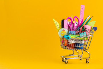 Shopping cart with School stationery on yellow background.