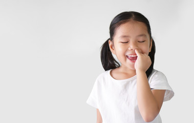Asian child cute or kid girl enjoy nose picking or picky by finger with eat snot and smiling happy with close eye on preschool or 5 years old and wear white t-shirt on white background with copy space