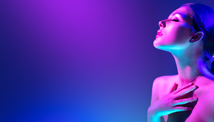 Spoed Fotobehang Beauty Fashion model woman in colorful bright neon lights posing in studio. Portrait of beautiful girl in UV. Art design colorful makeup