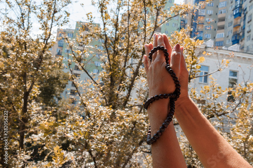Adult woman holding hands in Namaste gesture with Mala Beads